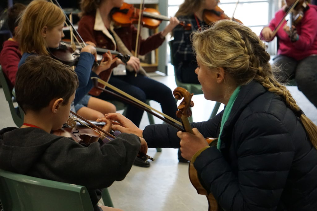 A teacher coaching young musicians