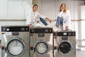 Two women sit on top of commercial washing machines, smiling