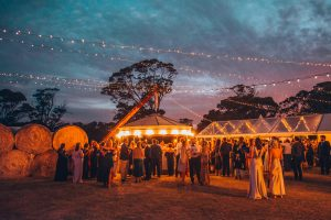A crowd in evening wear under fairylights, surrounded by gum trees and hay bales.