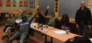 A group of Rangers sit around a table with their hands thrown up in the air