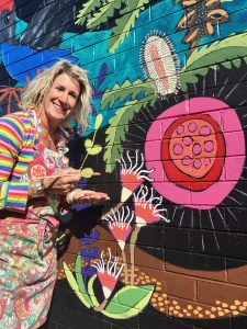 A woman in a rainbow striped shirt in the midst of painting a colourful mural of flora and fauna.